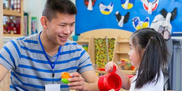 Male teacher playing blocks with student in classroom