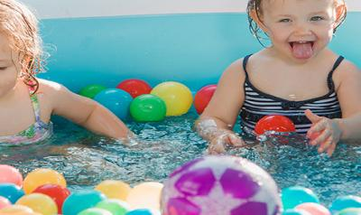 Toddlers playing with toy balls in pool