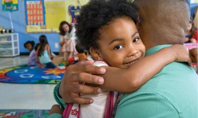 Girl hugging father in classroom