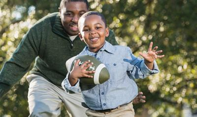 Father and son running and playing with a football outdoors