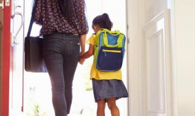 Mother and daughter walking out of a door to school