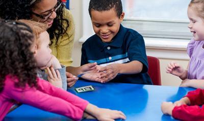 Teacher guiding preschool students at table
