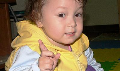 Toddler signaling with a pointer finger to wait