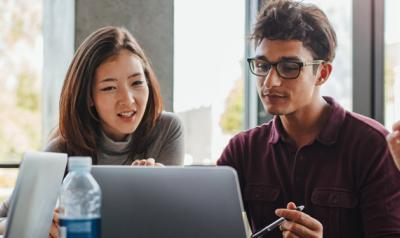 Adult students looking at a computer screen together
