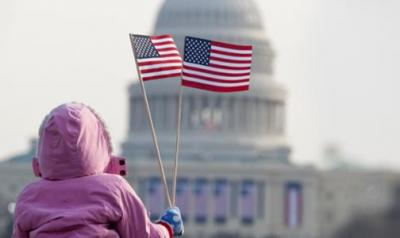 young child waves USA flag in front of the capitol building