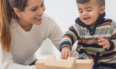 Mom and toddler son building with blocks