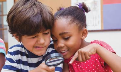 Two children looking through magnifying glass