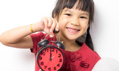 Young girl holding a clock.
