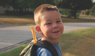 Child standing outside with backpack