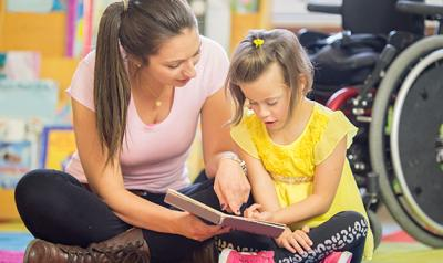 Teacher and student with a disability reading a book together