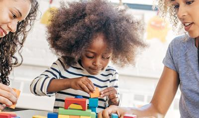 Two women and a young girl sitting at a table and playing with blocks