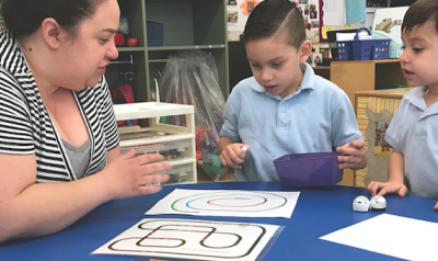 Teacher and students playing game with materials
