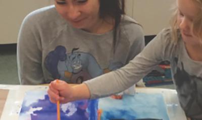 Teacher observes as child paints artwork