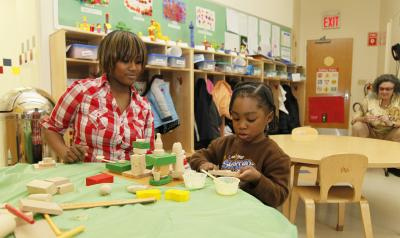An African-American educator interacts with a young African-American girl at a low table with blocks.