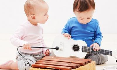 Two young children explore and play with musical instruments