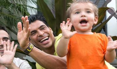 two parents with a young child clapping their hands