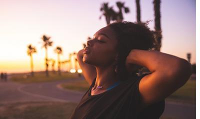 a person closing their eyes at a sunrise beach