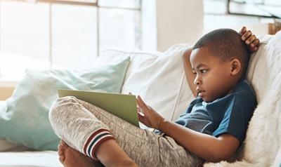 young boy learning on an ipad