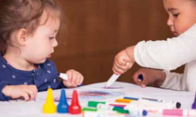 Two toddlers playing and drawing with assorted art materials