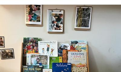 A bookshelf with children's books, some of which the children created.