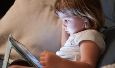 Preschool girl watching a digital tablet