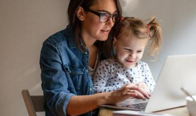 Young girl sitting her her mom's lap looking at the computer