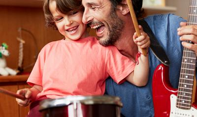 Father and son playing drums and guitar