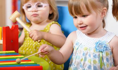Two young girls playing with a xylophone