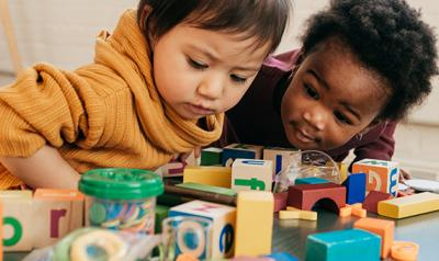 Two toddler girls playing with blocks
