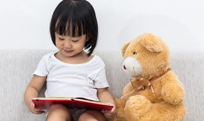 Young girl reading next to a teddy bear