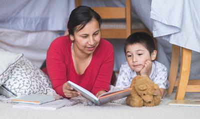 Mother and son reading a book on the floor of a child's room