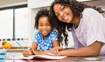 Mother and daughter at the kitchen table doing homework