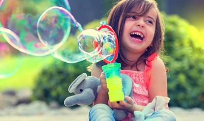 Young girl playing with a bubble machine