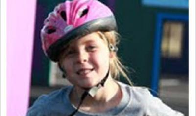 Young girl on a bike wearing a pink helmet