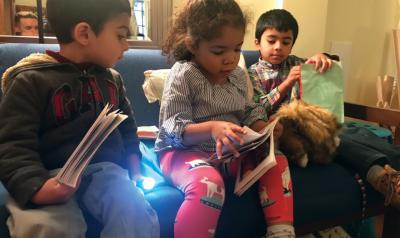 Three children reading a book