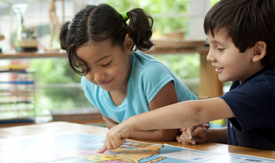 A young boy and girl pointing at a map on a desk in the classroom