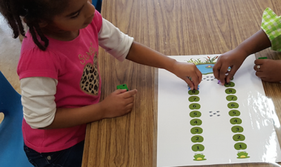 Two girls playing with lily pad math game