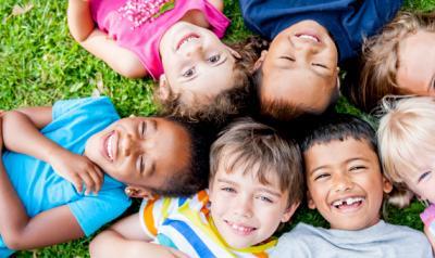 Seven children outside on the grass.