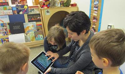 Teacher showing young children iPad
