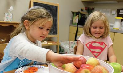 Two young girls with bucket of apples