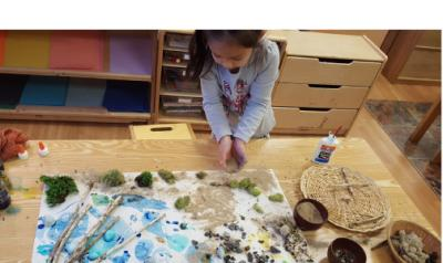 a child working on a craft project with grass, sticks, and sand