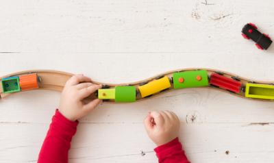 A child's hands can be seen guiding a toy train down a wooden track