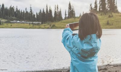 Child at a lake taking a photo with a smartphone