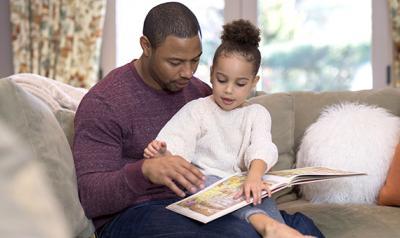 Young girl reading a book with her father