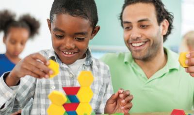 Teacher observing a child build a toy structure