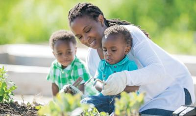 Teacher helping two preschoolers with gardening