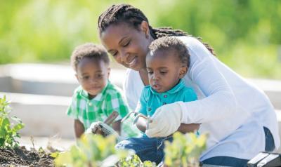 Teacher helping two preschoolers with gardening