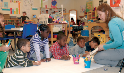 Teacher helping preschool class