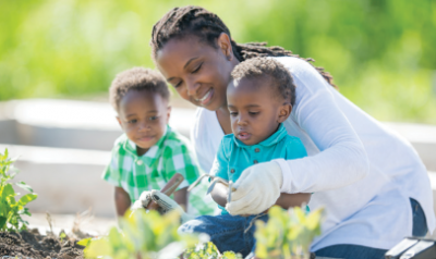 Mom helping toddler sons plant garden
