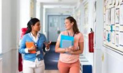 Two teachers walking down a school hallway